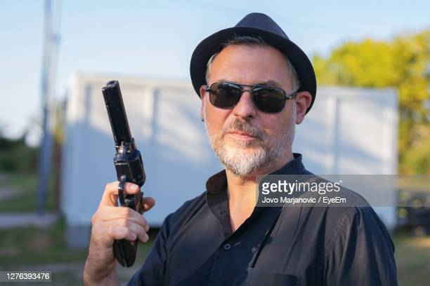 portrait of man holding sunglasses - gunman stock pictures, royalty-free photos & images