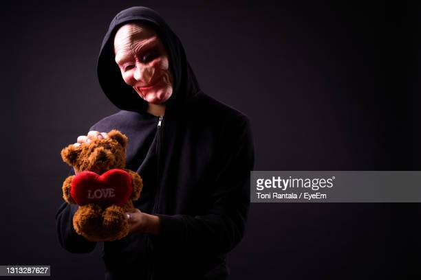 portrait of man holding toy against black background - bear suit stock pictures, royalty-free photos & images