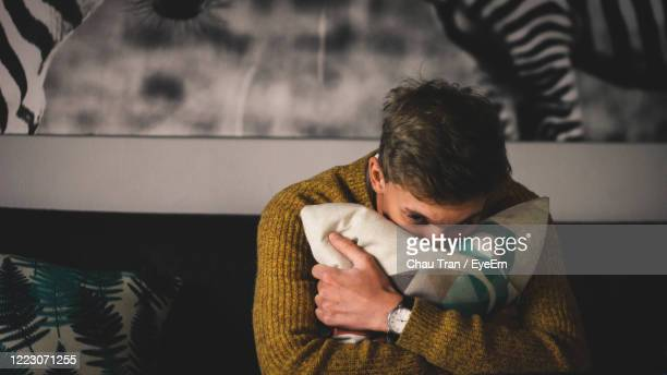 portrait of man hugging a pillow at home - sadness stock pictures, royalty-free photos & images
