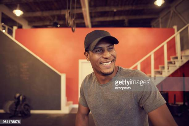 portrait of man in baseball cap looking away smiling - heshphoto stock pictures, royalty-free photos & images