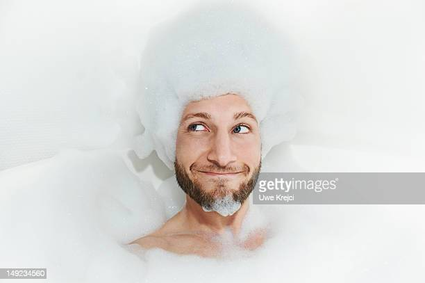 portrait of man in bath tub, foam on head - human body part stock-fotos und bilder