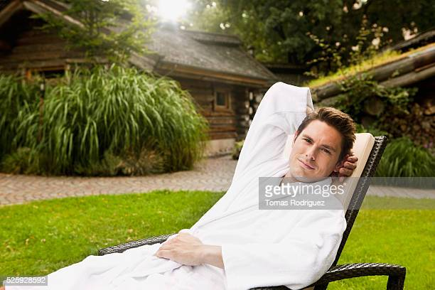 Portrait of man in bathrobe relaxing on lounge chair