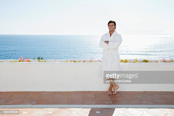Portrait of man in bathrobe standing on patio