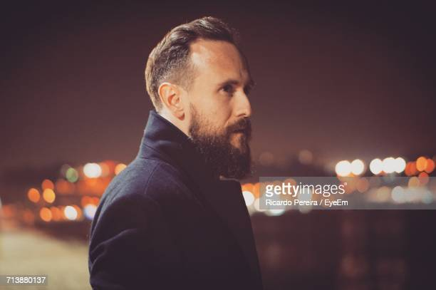 portrait of man in city against sky at night - one man only stock pictures, royalty-free photos & images
