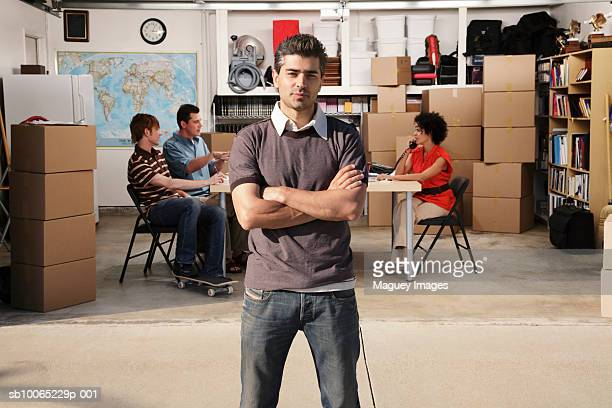 portrait of man in front of garage, three people talking inside in background - コスタメサ ストックフォトと画像