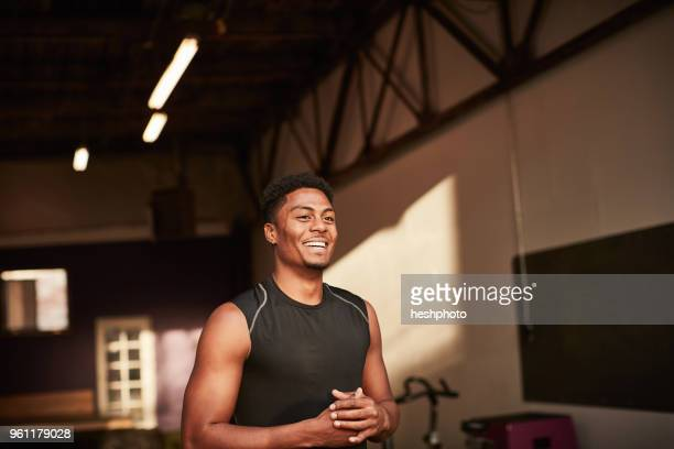 portrait of man in gym looking away smiling - heshphoto fotografías e imágenes de stock
