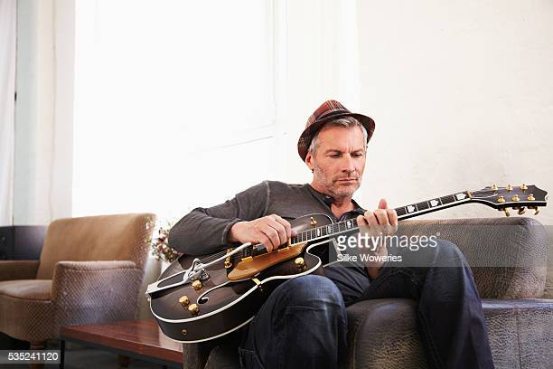 portrait of man in hat sitting at home and playing guitar - gitarre stock-fotos und bilder