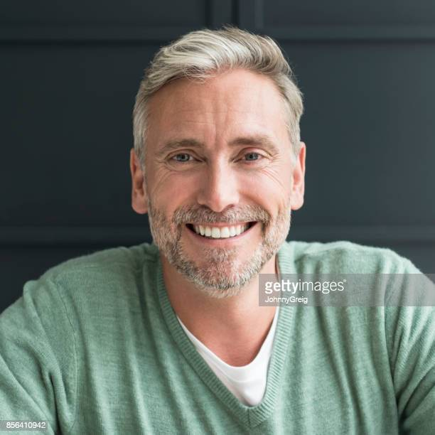 portrait of man in his 40s with grey hair and beard smiling towards camera - handsome older men stock pictures, royalty-free photos & images
