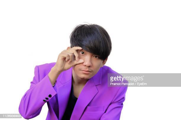 portrait of man in purple suit opening eye against white background - purple suit stock pictures, royalty-free photos & images