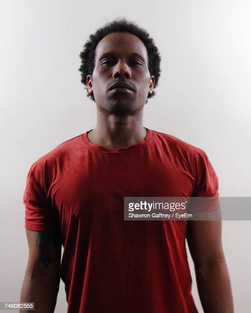 Portrait Of Man In Red T-Shirt Standing Against White Background