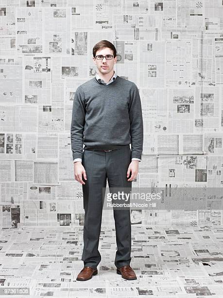 Portrait of man in room with walls covered with newspapers