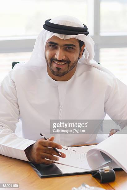 Portrait of man in traditional Middle Eastern attire signing papers, Dubai, UAE