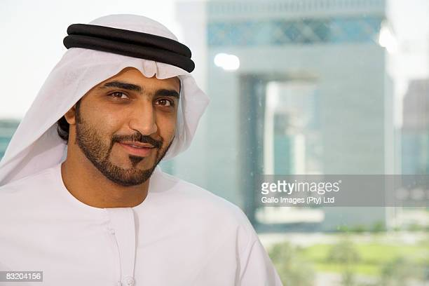 Portrait of man in traditional Middle Eastern dress, Dubai cityscape in background, UAE