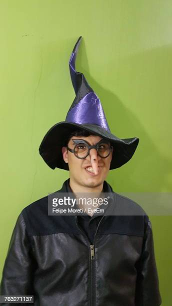 Portrait Of Man In Witch Hat And Artificial Nose Against Green Wall