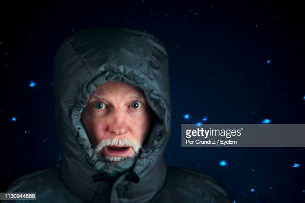 Portrait Of Man Ion Warm Clothing Against Glittering Background