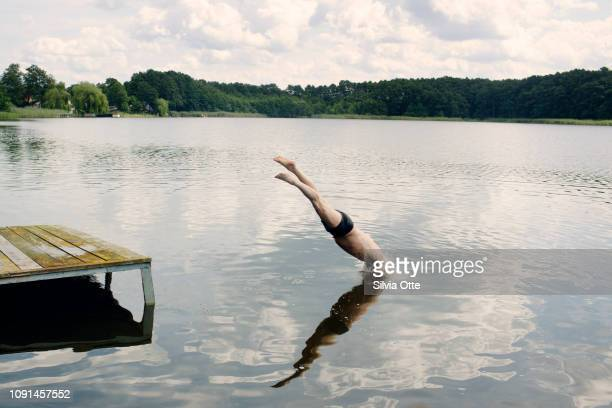 Portrait of man jumping from landing stage into water, going for a swim
