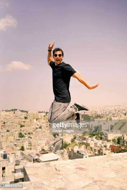 Portrait of man jumping on building terrace