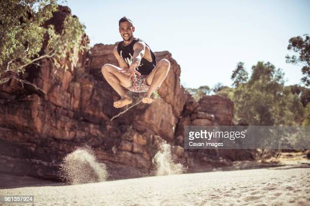 Portrait of man jumping on sand against sky at desert during sunny day