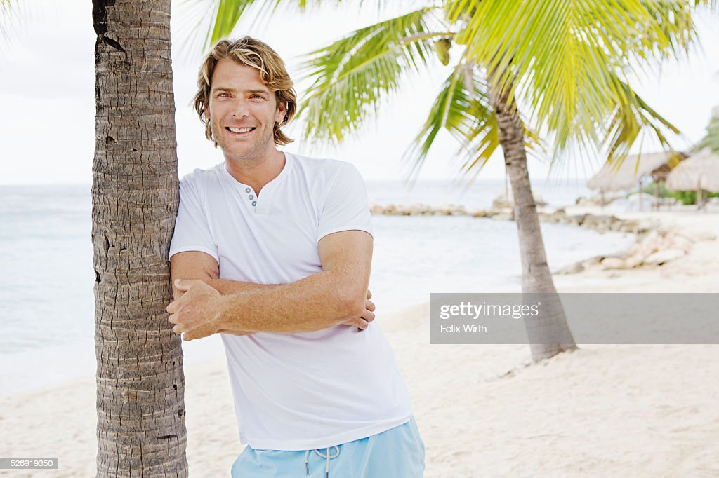 Portrait of man leaning against palm tree : Stock Photo
