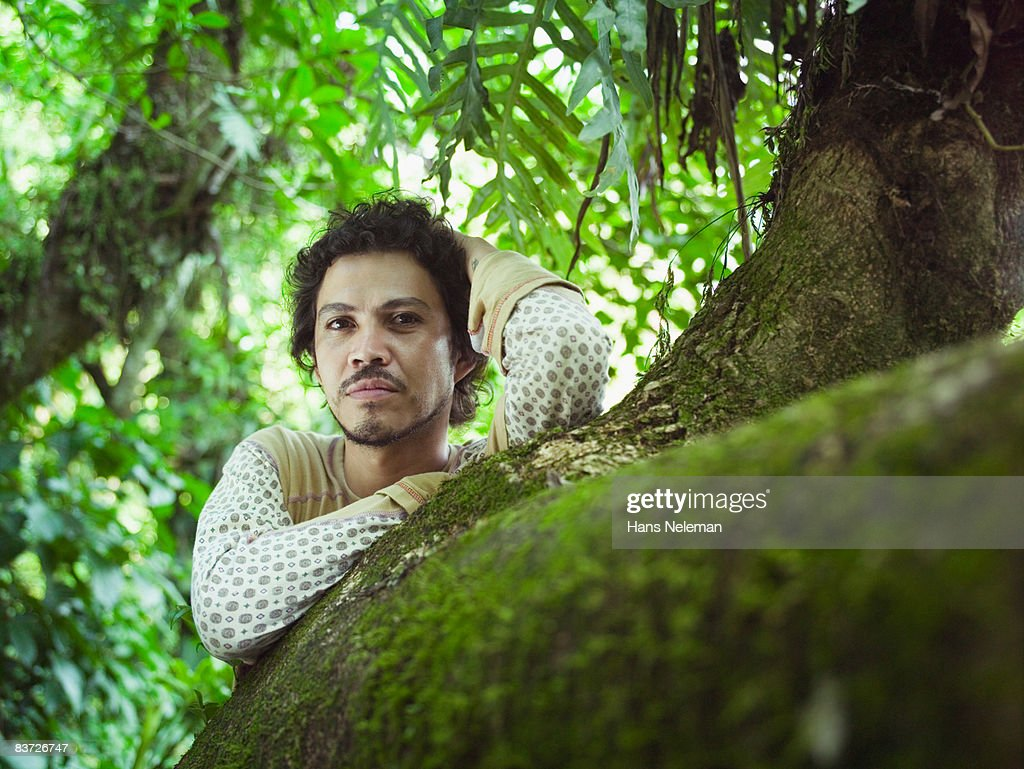 Portrait of man leaning against tree in jungle : Stock Photo