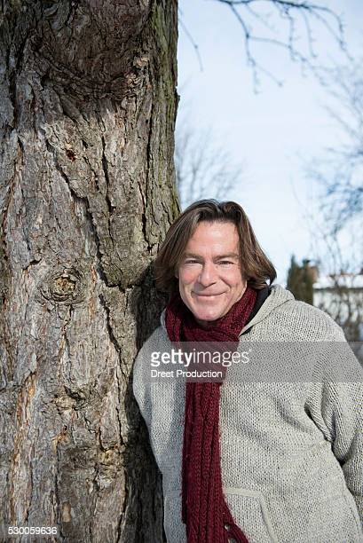 Portrait of man leaning by pine tree, Bavaria, Germany