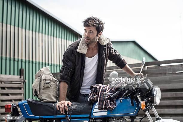 portrait of man leaning on motorcycle - stoppelbart stock-fotos und bilder