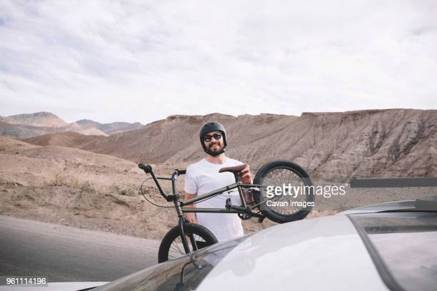 Portrait of man loading bicycle on car against mountains and cloudy sky