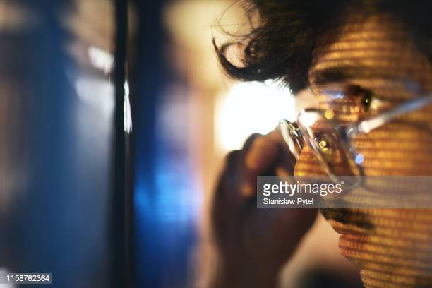 portrait of man looking on blue screen lit with binary code - big data - fotografias e filmes do acervo