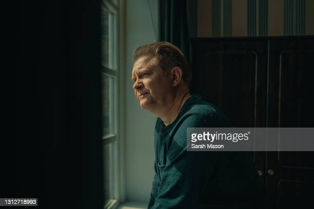 portrait of man looking out of window - only men stock pictures, royalty-free photos & images
