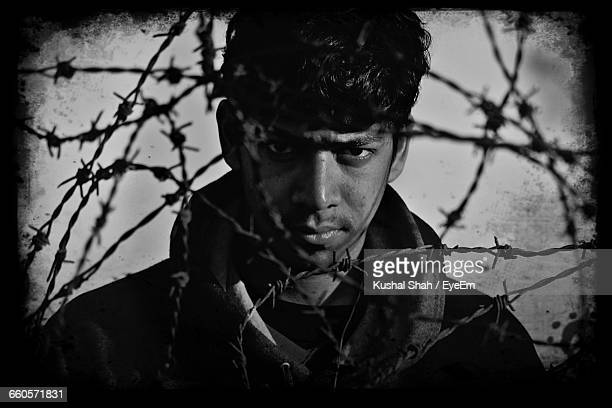 Portrait Of Man Looking Through Barbed Wire Fence