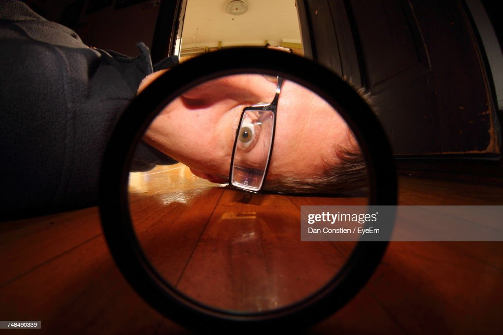 Portrait Of Man Looking Through Circle Shaped Glass On Floor At Home : Stock Photo