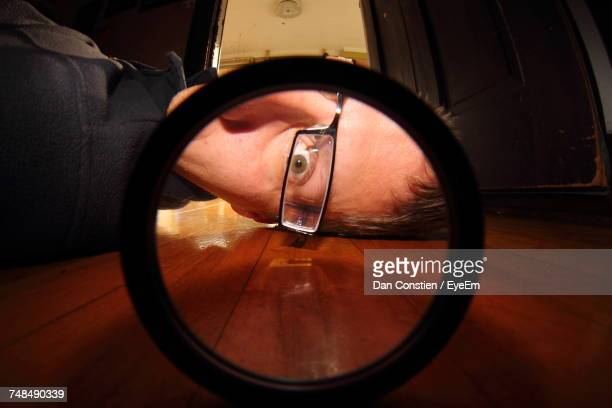 portrait of man looking through circle shaped glass on floor at home - floorboard stock photos and pictures
