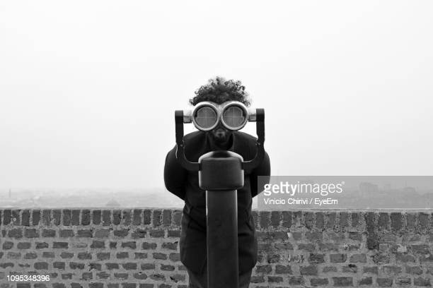 portrait of man looking through coin-operated binoculars at observation point - binoculars stock pictures, royalty-free photos & images