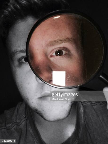 Portrait Of Man Looking Through Magnifying Glass In Darkroom