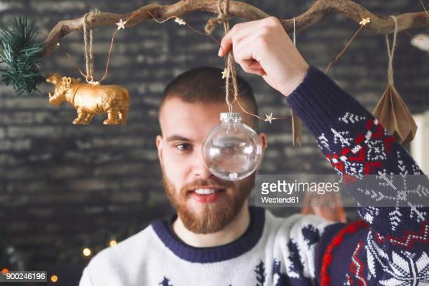 Portrait of man looking through transparent Christmas bauble