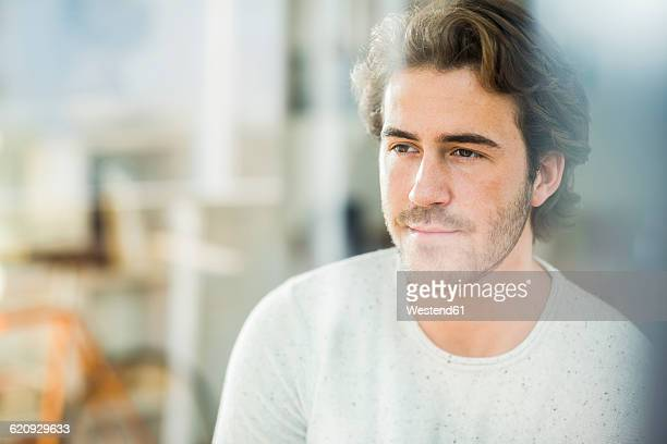 Portrait of man looking through windowpane
