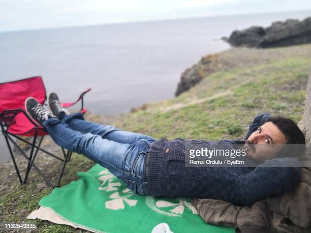 Portrait Of Man Lying Down On Cliff By Sea