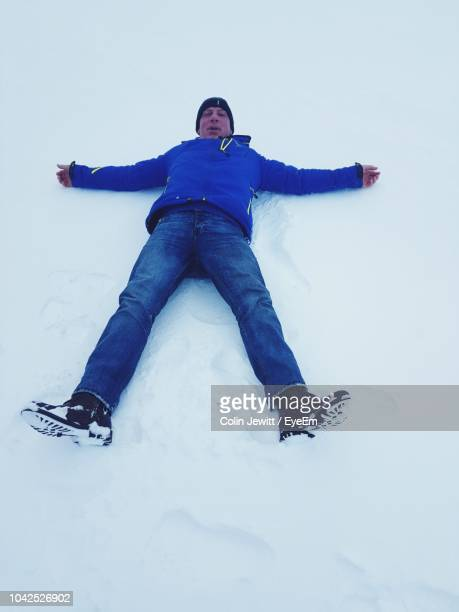 portrait of man lying down on snow - legs apart stock pictures, royalty-free photos & images