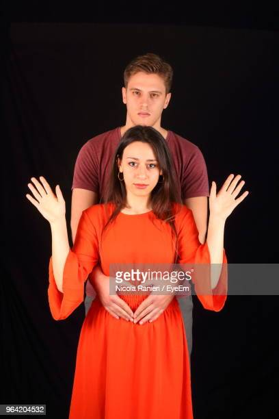 Portrait Of Man Making Heart Shape With Woman Against Black Background
