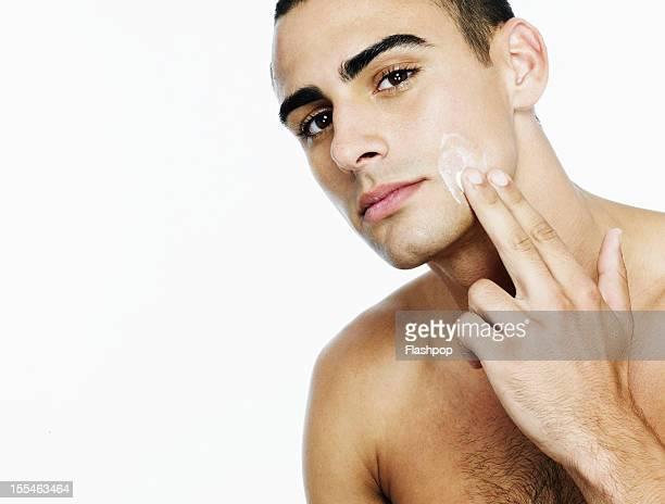 Portrait of man moisturising face