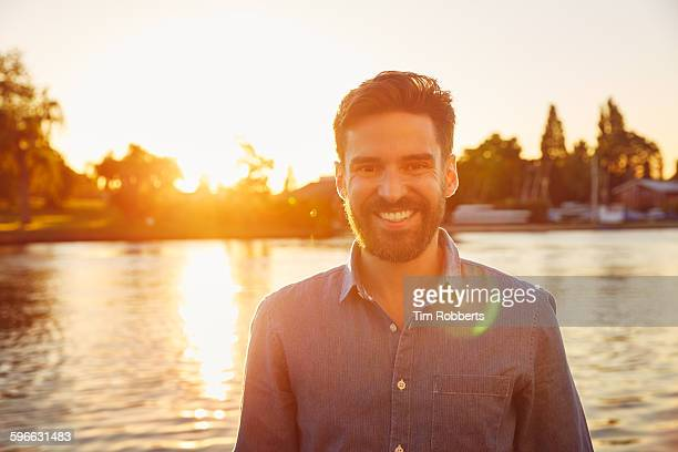 Portrait of man next to river at sunset.