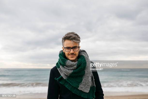 Portrait of man on the beach wearing knitted scarf