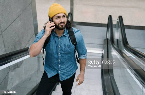 portrait of man on the phone using escalator - デニムシャツ ストックフォトと画像