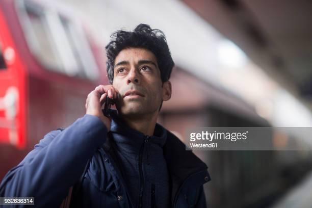 portrait of man on the phone waiting on platform - bahnreisender stock-fotos und bilder