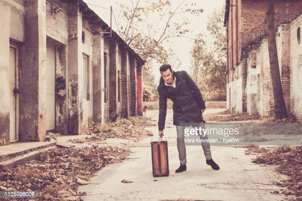 portrait of man picking up suitcase while standing on footpath amidst abandoned buildings - 防寒着 ストックフォトと画像
