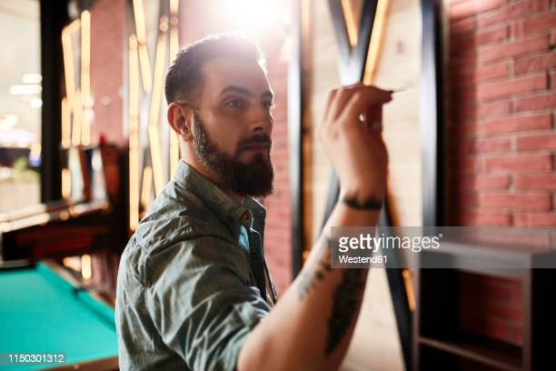 portrait of man playing darts - dart stock pictures, royalty-free photos & images