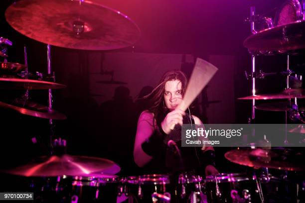 Portrait of man playing drums at concert