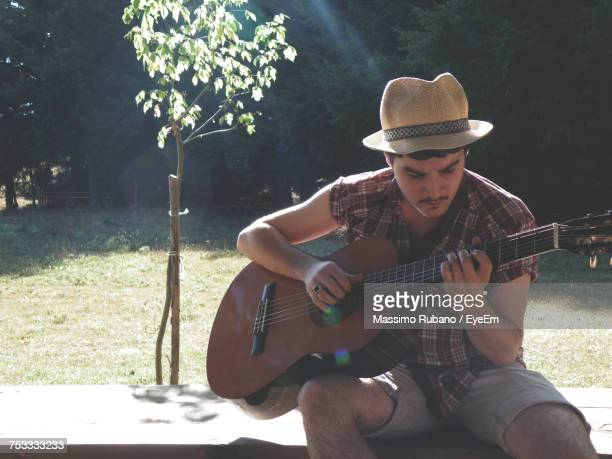 Portrait Of Man Playing Guitar In Park