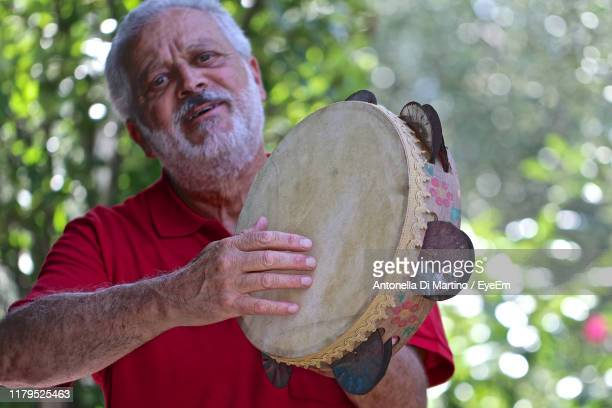 portrait of man playing tambourine while standing against trees - antonella di martino foto e immagini stock