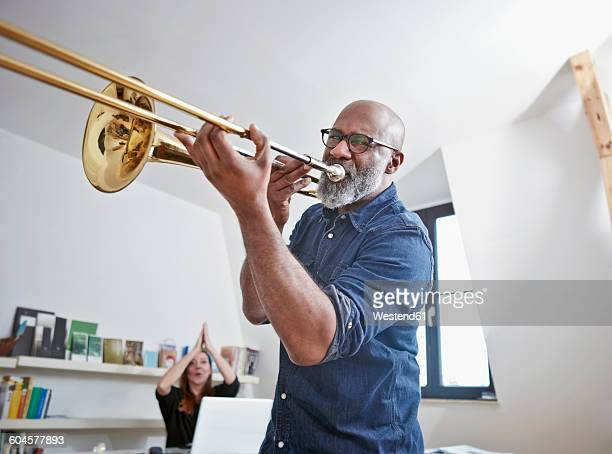 Portrait of man playing trombone at home office